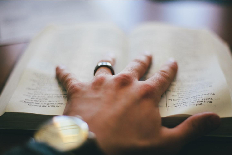 Mano agarrando biblia