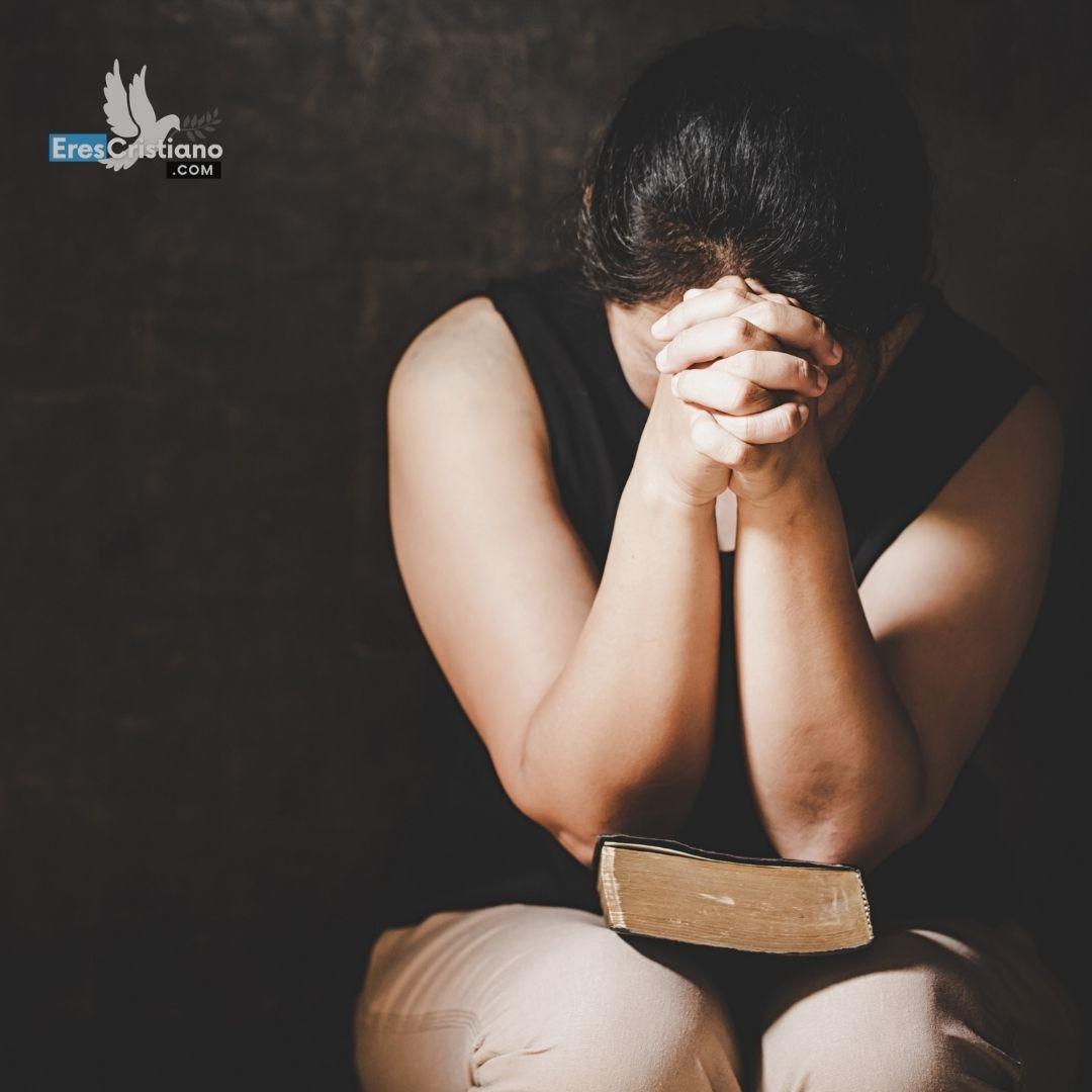mujer orando con los ojos cerrados