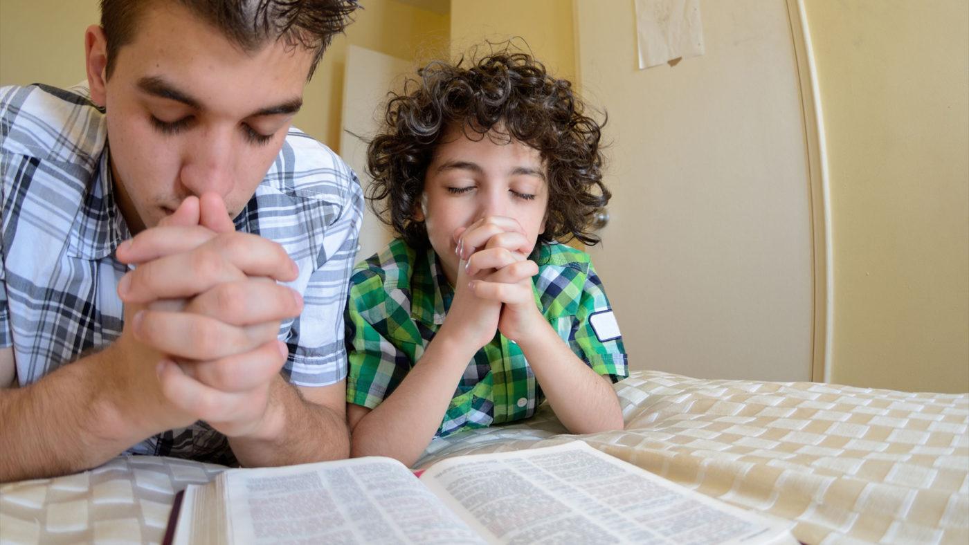 padres e hijo orando